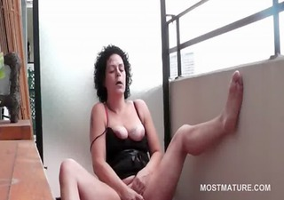 Curly orgasm craving mature masturbates on terrace